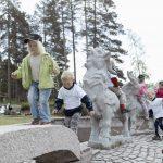 Barn som klatrer og leker på steinskulpturene i granitt av Bukkene bruse på Mineralparken på Evje