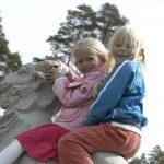 Jenter som sitter på en av Bukkene bruse i granitt i parken på Mineralparken på Evje