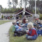 Barn og voksne koser seg med mat og drikke på plenen i parken på Mineralparken på Evje
