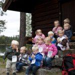 Mange barn sitter og spiser is i trappa til stabburet på Mineralparken på Evje