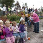 Barn og voksne som spiser i på steinbenken og rundt blomsterbedet på Mineralparken på Evje