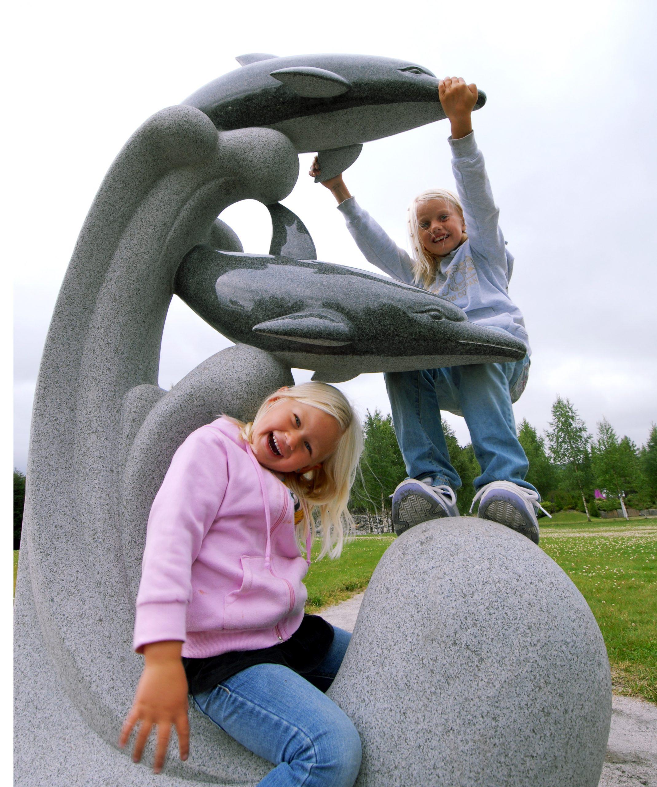 To blide barn klatrer i en stor delfinfigur i lys granitt som står i parken på Mineralparken på Evje