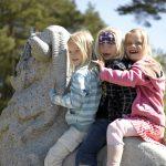 Blide jenter sitter på den største av de tre bukkene bruse på Mineralparken på Evje