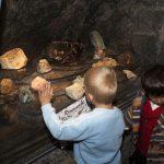 Barn på Dinosaurjakt mens de leter blant steinene etter dinosaurer i tunnelen på Mineralparken på Evje