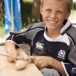 Blid gutt som former en figur av såpestein som er en aktivitet på Mineralparken på Evje