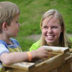 Barn får hjelp av ansatt til å vaske frem edelstener og fossiler fra sandposer i Eventyrbekken på Mineralparken på Evje