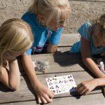 Tre barn sjekker på edelstenskortet fra Eventyrbekken hvilke forskjellige steiner de har funnet. etter å ha vasket sandposer i Eventyrbekken på Mineralparken på Evje.