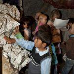 Barn som ser og tar på steinene som er utstilt i tunnelen på Mineralparken på Evje.