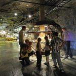 En familie som ser inne i et av de mange glassmonterne i tunnelen på Mineralparken på Evje.