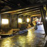 Bilder, utstyr og gamle gruvevogner i nedgangen til utstillingen i tunnelen på Mineralparken på Evje.