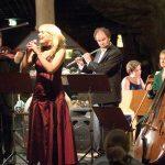 Orkester med fiolin, kontrabass, fløyte, piano og vokalist spiller inne i fjellet på Mineralparken på Evje.