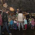 Barn og voksne går på skattejakt blant steinene inne i tunnelen på Mineralparken på Evje.